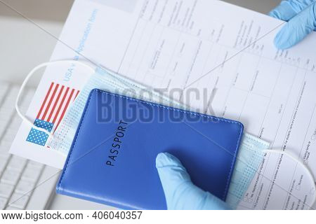 Hands In Rubber Gloves Holding Passport And Documents For Us Visa Closeup. Difficulty Traveling Abro