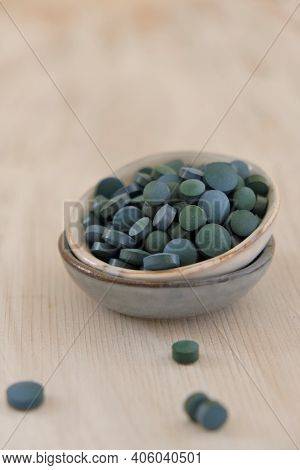 Spirulina Algae Green In Tablets In Ceramic Cups On A Light Wooden Shabby Background..dietary Supple