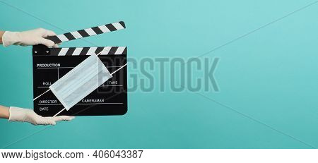 Hands With Grey Suit And Hold Black Clapper Board Or Movie Slate With Face Mask. It Use In Video Pro