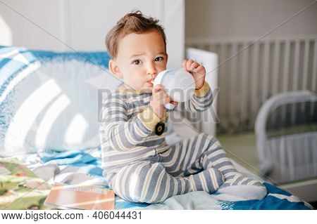 Cute Adorable Caucasian Kid Boy Sitting On Bed Drinking Milk From Kids Bottle. Healthy Eating Drinki