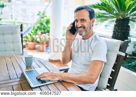Middle age man with beard smiling happy at the terrace working from home using laptop speaking on the phone