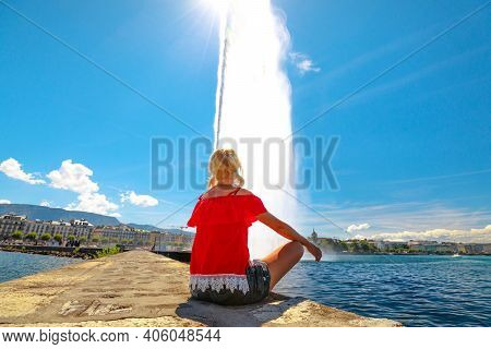 Blonde Tourist Woman Sitting A Pier, Looking Jet Deau Fountain Which Projects Its Water Spray 140 Me