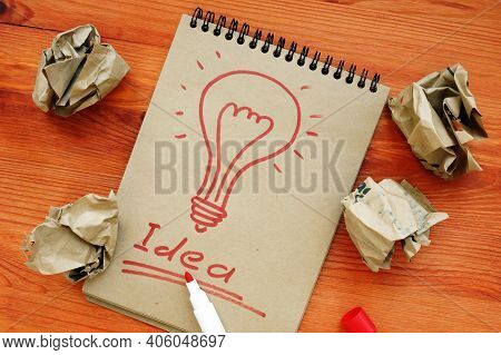 Idea Concept. Light Bulb As A Symbol Of Creativity. Success And Sheets Of Paper After Unsuccessful A