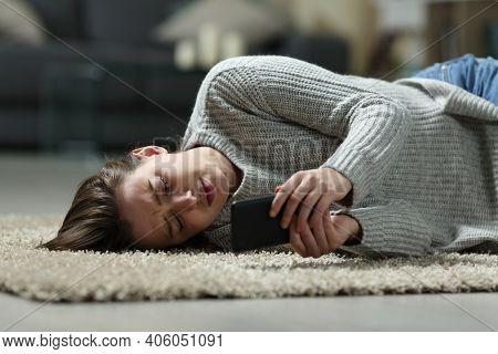 Sad Teen Reading Bad News On Smart Phone Lying On The Floor At Home