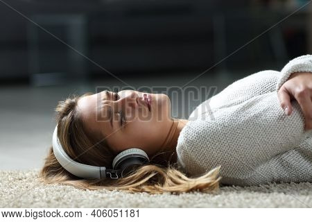Sad Woman Listening To Music Wearing Headphones Lying On The Floor At Home
