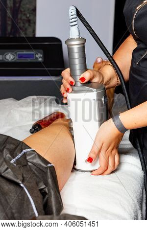 A Professional Beautician Performs An Electromagnetic Massage Of The Muscles In The Leg Using A High
