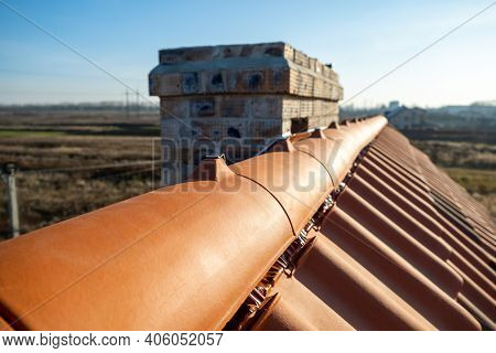 Closeup Of Yellow Ceramic Roofing Ridge Tiles On Top Of Residential Building Roof Under Construction