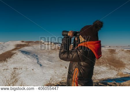 A Man Looks Through Binoculars For Nature. Tourist With Binoculars In The Mountains.