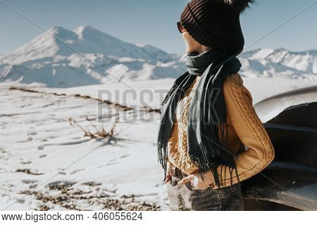 Travel To The Mountains By Off-road Vehicle. The Tourist Looks Into The Distance At The Snowy Mounta