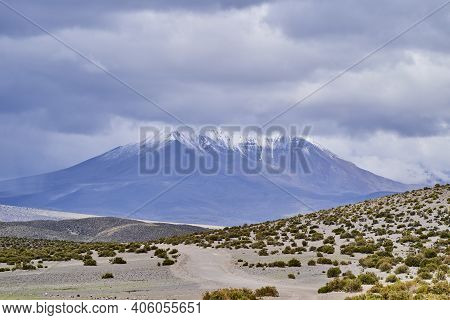 Snow Covered Mountains With Dramatic Sky In A Vast And Desolate Landscape At High Altitude In The Hi