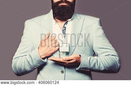 Masculine Perfume, Bearded Man In A Suit. Male Holding Up Bottle Of Perfume In Suit. Bearded Man Hol