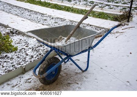 Beginning Of Winter. The First Snow Fell On The Garden Beds. Garden Equipment Is Unclaimed And Is Be