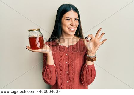 Young hispanic woman holding jar with honey doing ok sign with fingers, smiling friendly gesturing excellent symbol