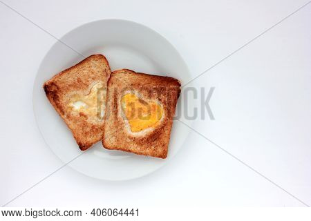 Toast Bread With Fried Egg In A Heart Shaped Hole On Plate On White Background. Creative Valentine's