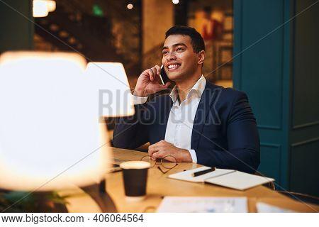 Joyous Dark-haired Male Entrepreneur Making A Call
