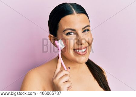 Beautiful brunette woman using facial exfoliating brush looking positive and happy standing and smiling with a confident smile showing teeth