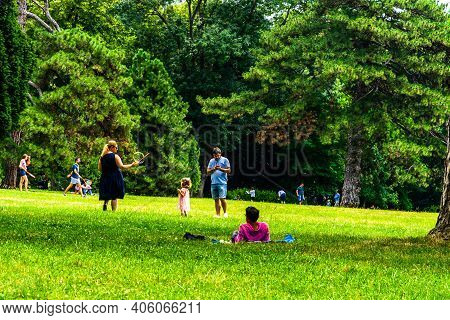 Mother Making Soap Bubbles For Herlittle Daughter, People Having Picnic Relaxing And Having Fun Duri