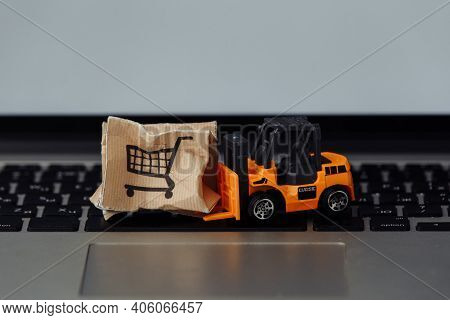 Toy Forklift With Box On A Laptop. Logistics And Wholesale Concept