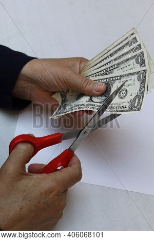 Cut To The Budget, Hands Of A Woman Grasping American Dollar Bills And Scissors