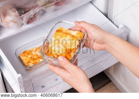 A Person Is Taking A Container Of Frozen Casserole Or Lasagne Out Of The Freezer. Concept Of Ready M