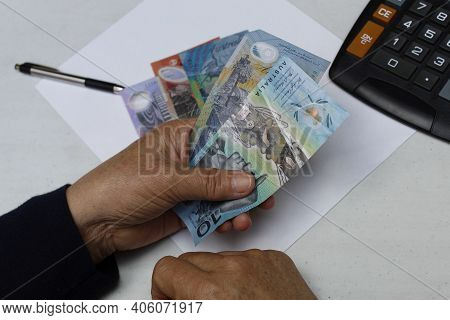 Hand Of A Senior Woman Holding Australian Banknotes With A Pen And Calculator On The Table