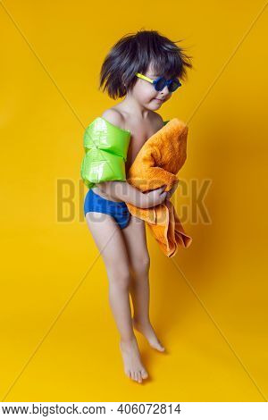 Boy Child In Inflatable Green Swim Armbands And Sunglasses Stands On A Yellow Background In The Stud