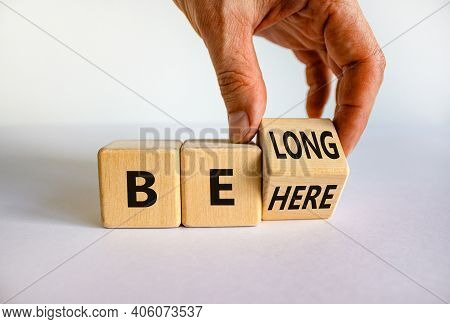 Be Here Belong Symbol. Businessman Hand Turns A Cube And Changes Words 'be Here' To 'belong'. Beauti