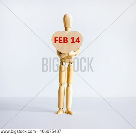 February 14 Valentines Day Symbol. Wooden Model Of A Human Holding A Wooden Heart With Words 'feb 14