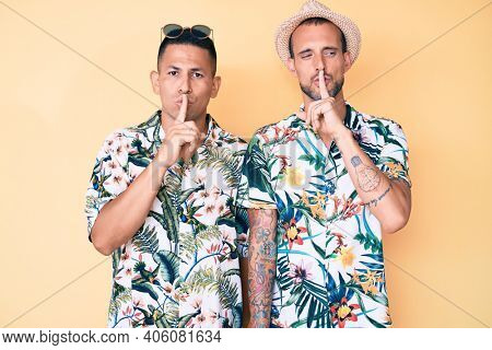 Young gay couple of two men wearing summer hat and hawaiian shirt asking to be quiet with finger on lips. silence and secret concept.