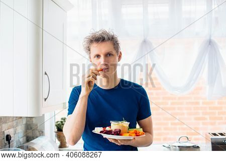 Young Man Eating Carrot Stick With Hummus Dip On The Kitchen. Hummus Served With Raw Vegetables On T