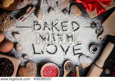 Baked With Love Written On Flour. Gingerbread Heart Shaped Cookies, Spices, Coffee Beans And Baking