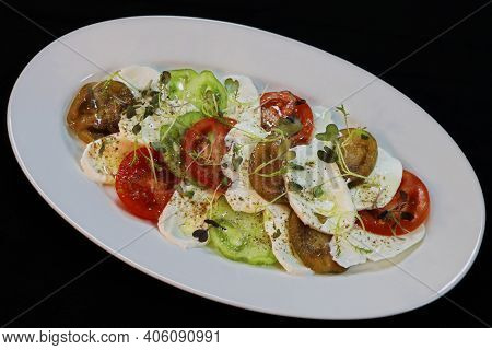 Heirloom Tomatoes And Mozzarella Salad In A White Plate With Black Background
