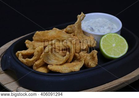 Fried Anchovies With Tartar Sauce And Lime Wedge In A Serving Dish