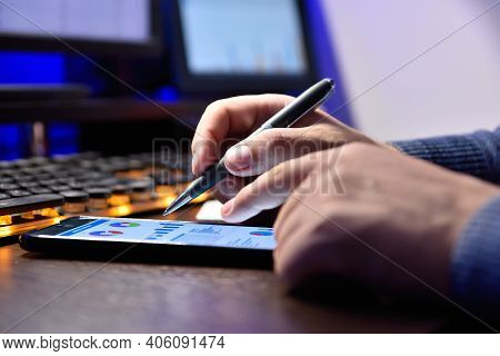 Businessman Sitting In Night Office And Using Mobile Phone With Stock Chart. Investment And Financia