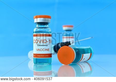 Covid-19 Vaccine And Syringe Injection On Blue Table. Healthcare And Corona Virus Vaccination Concep