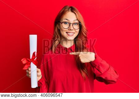 Young redhead woman holding graduate degree diploma pointing finger to one self smiling happy and proud