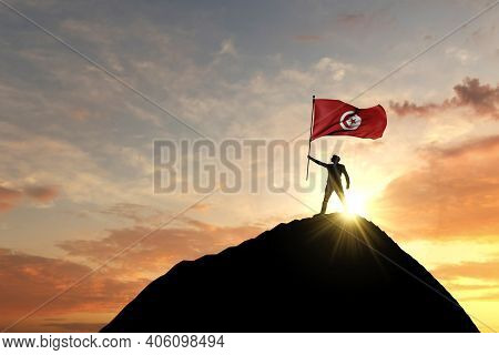 Tunisia Flag Being Waved At The Top Of A Mountain Summit. 3d Rendering