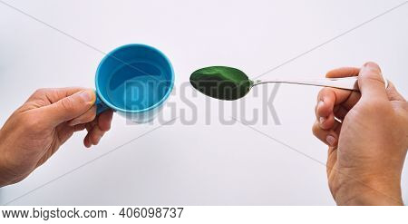Man Hands Holding Cup Of Water And Spoon With Chlorella, Spirulina Or Wheatgrass. Detox Juice Prepar