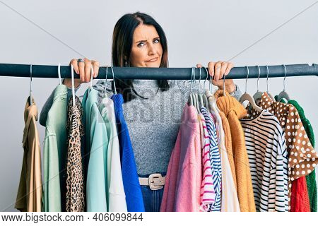 Middle age brunette woman working as professional personal shopper skeptic and nervous, frowning upset because of problem. negative person.