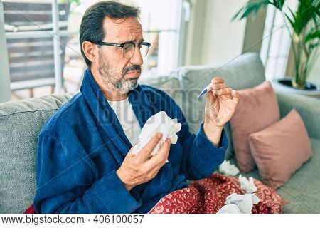 Middle age man feeling sick with cold and fever at home, ill with flu disease sitting on the sofa