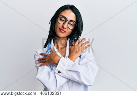 Beautiful hispanic woman wearing doctor uniform and stethoscope hugging oneself happy and positive, smiling confident. self love and self care