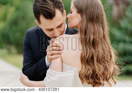 Beautiful, Gentle And Happy Bride And Groom. Man Gently Kisses Womans Shoulder