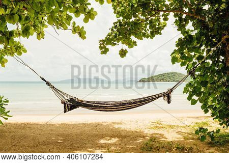 Hammock With Trees On A Beautiful Beach At Sunset