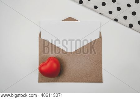 Blank White Paper Is Placed On Open Brown Paper Envelope With Red Heart And White Cloth  On White Ba
