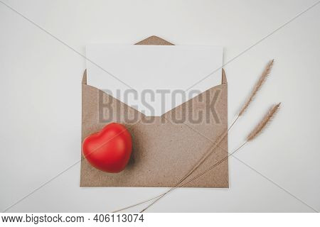 Blank White Paper Is Placed On Open Brown Paper Envelope With Red Heart With Bristly Foxtail Dry Flo