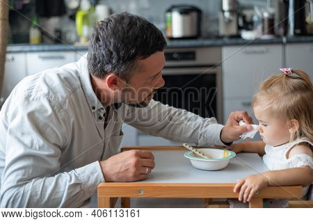 A Caring Man With A Beard Feeds His Little Daughter. A Little Girl Sits At A Childrens Dining Table