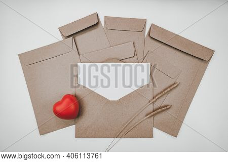 Blank White Paper Is Placed On The Open Brown Paper Envelope With Red Heart And Bristly Foxtail Dry