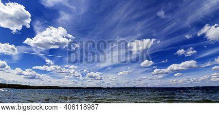 Dark Blue Sky With White Cumulonimbus Clouds Over Morning Lake