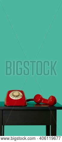 a red landline rotary dial telephone, with its handset off the hook on a black wooden table, on a green background, in a vertical format to use for mobile stories or as smartphone wallpaper