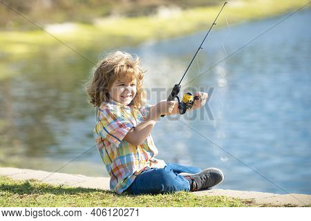 Young Fisher. Child Fishing. Kid With Spinner At River. Portrait Of Excited Boy Fishing Jetty With R